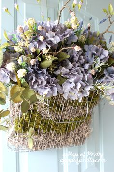 Summer door decor idea. Tired of wreaths? Fill a wire basket with moss and florals instead.