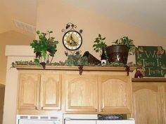 Lady Goats Decorating Above Kitchen Cabinets With Ivy Ferns