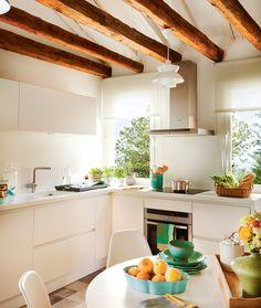 Cocina con office en blanco, con vigas de madera y mobiliario exento de tiradores