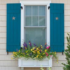 closeup of blue, open board-and-batten shutters with a star-shaped cut-out attached to a white-trimmed window on a house with beige siding, and a colorful flower-box below the window