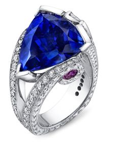 Engraved platinum ring featuring a 11.87ct tanzanite accented with 2.77ctw of white diamonds, and pink sapphires.