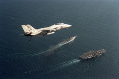 A Fighter Squadron 2 (VF-2) F-14A Tomcat aircraft passes over the aircraft carrier USS RANGER (CV-61) and an Iowa-class battleship. VF-2 is deployed aboard the RANGER. Photo taken in September of 1987.
