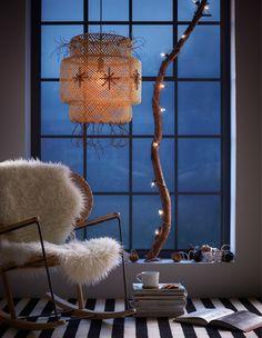 Ein großes Fenster mit einer Bambusleuchte, die weihnachtlich dekoriert ist. Auf der Fensterbank dahinter steht ein großer Ast, der mit einer Lichterkette dekoriert ist.