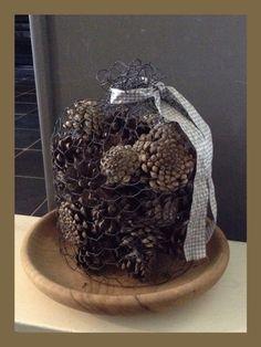 Decoratie #herfst: #dennenappels in een stolp van gaas op een oud houten bord.
