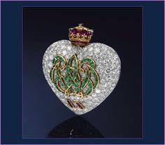 REGALITÀ GIOIELLI: AS JÓIAS DE WALLIS SIMPSON - A MULHER QUE FEZ UM REI ABDICAR O TRONO  Realizado por Cartier em 1957, para comemorar o vigésimo aniversário de casamento dos duques, este broche de coração com as iniciais do casal entrelaçadas foi feito a partir de rubis, esmeraldas e diamantes que pertenciam à coleção de joias do duque.