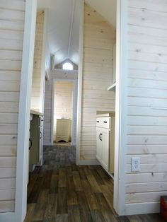 The tiny house has a main floor bedroom with closet and a kitchen in the middle that separates the living room from the bedroom.
