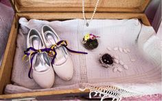 Wedding theme: Lovebirds Wedding colours: purple & yellow  The bride's accesories in a very very old suitcase