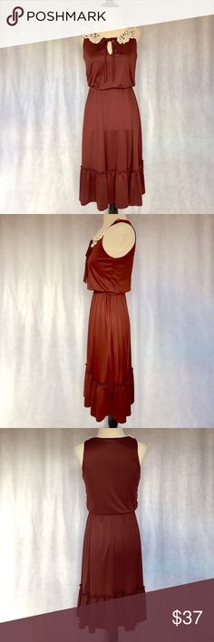 Vtg 70s XS S Indian Red Prairie Ruffle Midi Dress This vintage dress features sleeveless style, crochet trim collar, tie front, fully elastic waist, full bottom, ruffle hem, & midi length. Bodice is lined; bottom is unlined. Gorgeous color (truest color shown in close up). Pulls on/off over head. Has a few flaws in manufacturing stitching & small repair (see pics). Price reflected.  Brand: Dalil Material: N/A (Feels like Polyester) Size: 9 (Fits like an XS/S) Bust: 32-36 Waist: 22.5-30 Hips…