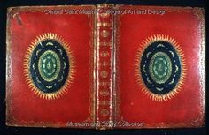 The Book of Common Prayer,  Very ornate binding; sewn on 4 sewing stations; full bound in grained red morocco; head bands of multi-coloured silk; central black morocco oval onlay, with green morocco oval onlay with flame design round the edge, angels on the back, more angels and JHS in centre; gold tooled key pattern rolled borders with angels in the corners; 6 panels on spine interspersed with ornate pallet lines and oval motifs in each panel.