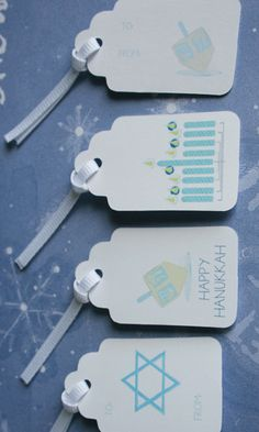 """Pack of 8 Hanukkah gift tags. 2"""" gift tags come ready to add to your holiday gifts. Celebrate with a dreidel, menorah, Happy Hanukkah, and Star of David gift tags. Artist designed and handmade."""