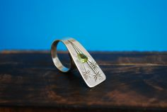 One of a kind sterling silver ring with trillion cut Peridot stone. Unique design with hand-engraved dandelions. This handmade silver ring will bring