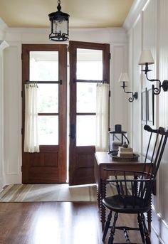 White painted wainscoting, beadboard, crown moulding, Early American, Windsor Chair, Front entry, foyer, Wooden French doors, wrought iron light fixtures {Why I'm Loving White Walls — Stevie Storck Design Co.}