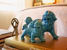 A pair of glazed blue ceramic foo dog (or foo lion) statues top a stack of books on this tabletop. The Chinese collectibles add color and character to this otherwise neutral space.