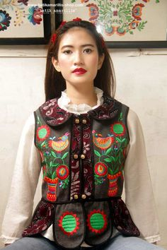 Batik Amarillis made in Indonesia  batik amarillis's piccola vest  features Ukrainian embroidery inspired meets tenun batik  gedog Tuban,Indonesia. Take a fresh, sweet & whimsical approach to power dressing with this Krakow-Poland classic traditional folklore inspired jacket.  The beauty essential is reworked with a contrast-coloured batiks,unique cuttings ,trims,glossy beaded buttons,it has fitted waist with unique peplum petals