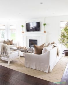 Cozy Fall living room with neutral tones and greenery accents.  I love our York Pottery Barn sofa and our new fireplace! Early Fall home tour with fall decor. #kitchencabinets #falldecor #fallstyle #home #homedecor #homedesign #living #livingroomideas #livingroomdecor #livingroomdecorideas #livingrooms