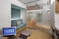The treatment pod includes art-glass doors that look to the garden zone beyond; there's also a guest seating niche on the left. The patient treatment chairs feature touchscreen monitors that control each pod's lights and temperature, as well as provide digital connectivity to the Internet and entertainment options. The Brooklyn Infusion Center. Photo credit: John Bartelstone Photography; Chun Y Lai.