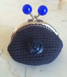 Portamonete realizzato a mano con uncinetto, blu scuro con rosa in raso blu applicata sul davanti. Chiusura a scatto con sfere color blu elettrico.