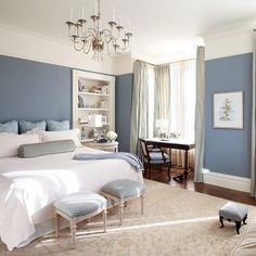 Keep darker, muted blues from becoming dreary by balancing them with lighter colors. The darker shade of blue used on the walls adds elegance to this master bedroom. The large cream-color area rug and white bedding keep the room feeling open and airy despite the walls? rich shade