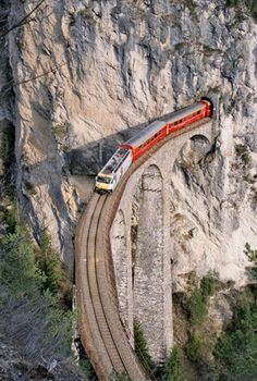 Landwasser Viaduct - Switzerland. It looks like the train just manages to squeeze through that tunnel. Tight.