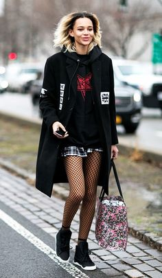 Binx Walton wears a graphic hoodie, black coat, plaid miniskirt, fishnet tights, and high-top sneakers