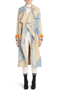 Bands of leather in vibrant orange trim the cuffs of this beautifully draped, silk-blend trench coat woven with a stunning French-blue fil coupé floral print that adds rich texture to the chic silhouette.