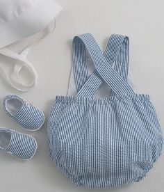 One piece summer sunsuit in blue and white striped seersucker cotton. Side front openings, elastic back waist, cross-over straps and bib pocket. White linen buttons Fully lined with cotton lawn. Shown here with the white linen bucket hat and baby espadrilles (Accessories). 55/45% cotton/poly. Hand or machine wash 40°C.
