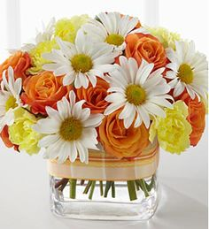 Orange spray roses, yellow miniature carnations and white traditional daisies