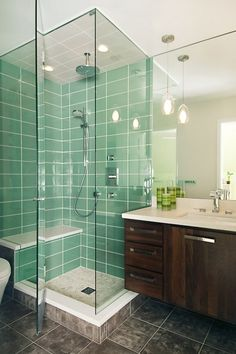 Love the glass shower with the gorgeous green tile.  This is the exact color I would want a bathroom to be.