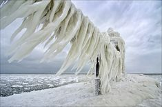 Driving winds from the North along with splashing waves created a curved wall of ice resembling dinosaur teeth hanging from the catwalk leading to the outer light of the St. Joseph, Michigan lighthouse. The catwalk deck is about ten feet above the pier, the ice teeth hang down to the pier in some place