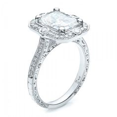 This beautiful engagement ring was custom designed for a bride by Joseph Jewelry.  A radiant cut center stone is accented by a halo of bright cut set and bezel set diamonds trimmed with milgrain and hand engraving.