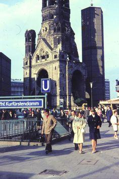 """Menschen laufen an der U-Bahn-Haltestelle """"Kurfürstendamm"""" vorbei. Im Hintergrund ist die Kaiser-Wilhelm-Gedächtniskirche, besser bekannt als """"Hohler Zahn"""", zu sehen. 1960er - WDR Digit"""