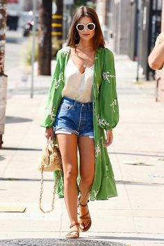 Emily Ratajkowski took your basic jorts and tank combo to the next level with an inspired style decision: wearing a wrap dress as a lightweight coat. It's a summer dressing solution & we wish we thought of ourselves, but we'll settle for copying her outfit instead. Love the pop of green!