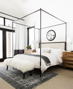 """""""We kept all selections high contrast to keep things feeling crisp and modern,"""" says Shea. """"Every piece selected has clean lines but lots of variation in texture."""" A Ballard Designs mirror hangs above an RH bed in the guest suite; the bench was custom, the vintage rug is from RH, and the dressers are by Noir."""