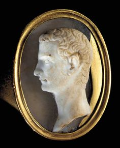 A ROMAN ONYX CAMEO PORTRAIT OF CALIGULA   Circa 37-41 A.D.   The idealized portrait sensitively sculpted, the emperor in profile to the left, with a broad forehead capped with typical Julio-Claudian short curly locks but with a noticeable and characteristic hollow at the temple, the face with a deep-set eye, slender nose, characteristic protruding upper lip, and narrow chin; mounted in a modern gold finger ring  1 1/16 in. (2.7 cm) long