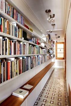 come sfruttare un lungo corridoio Il corridoio è progettato come un locale polifunzionale, grazie alla lunga cassa panca collocata sotto le mensole cariche di libri.