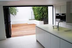 Kitchen Bi-folding doors with small patio. Love the green overhang outside. Kitchen Dining Living, Kitchen Decor, Kitchen Ideas, Dream Home Design, House Design, Devon House, Kitchen Renovation Inspiration, Open Concept Kitchen, House Inside