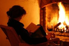 A book, a glass of wine and a fireplace.