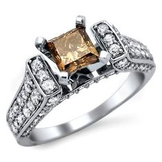 Fancy Brown Princess Cut Engagement Ring - Here's a very rare & pretty 1.70 carat Fancy Brown Princess Cut Engagement Ring set in 14k White Gold. It's an excellent cut SI1 in diamond clarity with a .70 carat Solitaire Brown Princess Cut Diamond is set atop of the item. Also 1.0 carats of round white diamonds surround the solitaire. They are sparkling stones set around the top, down its sides & on its front & back. Its top measures 5.25mm wide along at its largest point…