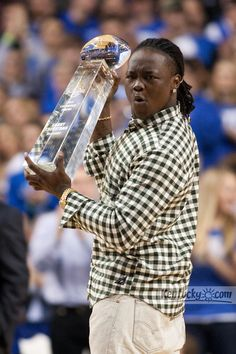 Former UK Football player Danny Travathan accepts the Nat'l Linebacker of the Year award from the College Football Performance Awards during a timeout in the first half. UK hosted Ole Miss Saturday, Feb. 18, 2012 at Rupp Arena in Lexington . Photo by JONATHAN PALMER — Herald-Leader