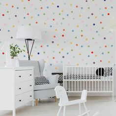 An assortment of mini 1 inch Rainbow Confetti Dots on a white wall with a white crib in-front and a white floor lamp with black base and green plant. White rocking horse and light grey sitting chair beside a white dresser with on top. Confetti Wall, White Floor Lamp, Black Floor, Floor Lamps, Vinyl Wall Stickers, Textured Walls, Home Interior, White Walls, Girls Bedroom