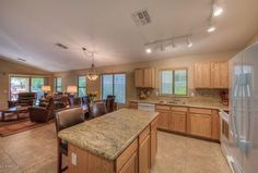 Contemporary Kitchen with limestone tile floors, Golden Cascade Granite Countertop, Legend Recessed Panel Cabinets, L-shaped