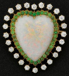 EDWARDIAN OPAL HEART BROOCH WITH DIAMONDS AND DEMANTOID GARNETS The shaped opal is framed by a line of thirty-eight faceted demantoid and twenty-four OEC diamonds