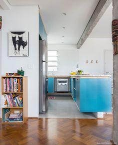 Cozinha integrada com marcenaria revestida de fórmica azul.