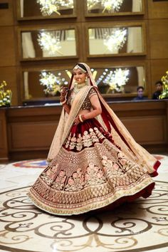 Bridal Wear - Bride in a Marsala and Gold Lehenga with a Beige Net Dupatta | WedMeGood | Wedding Planning by: Shloka Events #wedmegood #indianbride #indianwedding #bridal #bridallehenga #bridaloutfit #indianwedding #lehenga #marsala #golden