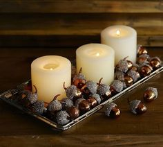 dip some acorns in metalic paint and glitter to dress up  simple white candles.