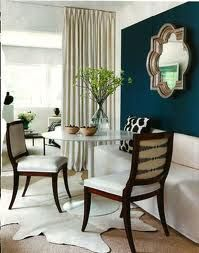 Contemporary dining nook with navy wall, quatrefoil mirror, white furniture and a hide rug. Lots of light and beautiful greenery too. #dining #classic