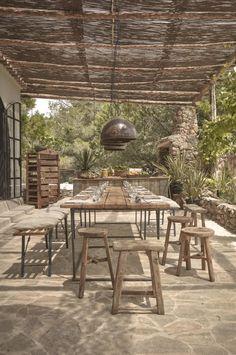 A woven cane pergola shades an outdoor dining patio. #gardenista #ibiza #pergola #outdoorliving #gardenideas