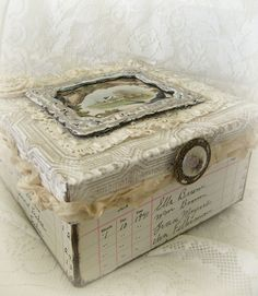 Altered box, covered with vintage ledger paper, laces, ribbon, ornate button, framed vintage image of birds, and more