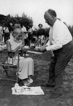 Alfred Hitchcock serving tea to Grace Kelly on the set (1954).
