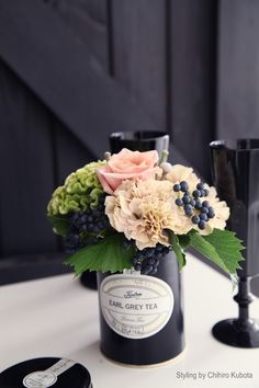 Fall arrangement styling- love pop of colors with black vase; dark berries, light peach mixed with green and black